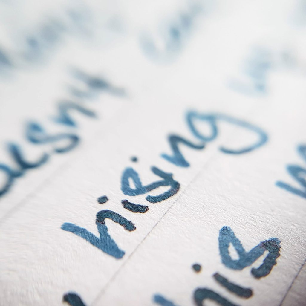 Writing sample of Taccia Navy Blue Jeans ink on Traveler's Company notebook
